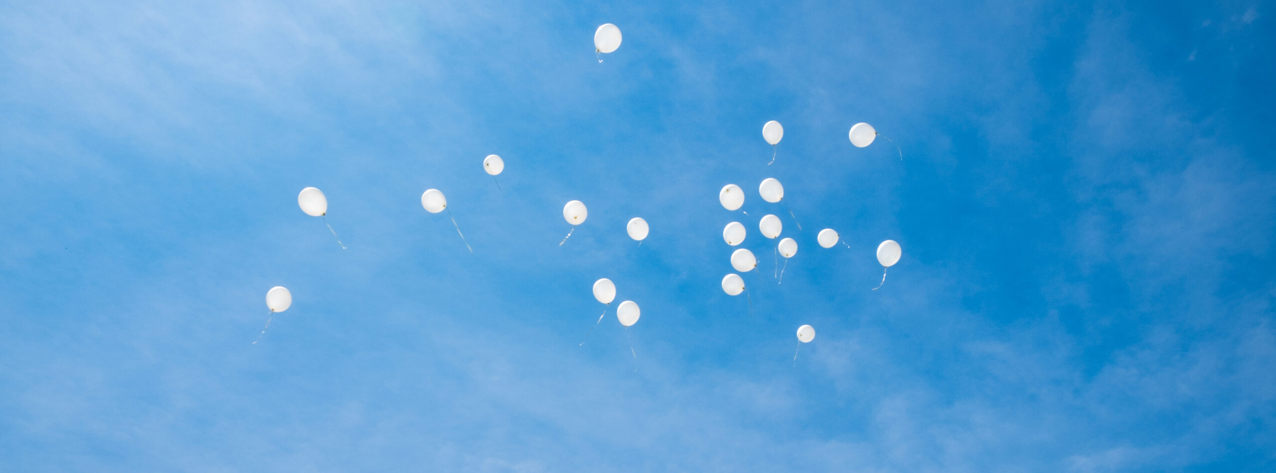 White,Balloons,Flying,Up,In,The,Sky.